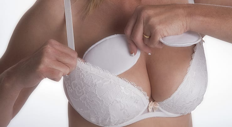 Woman stuffing her white bra to make her breasts look bigger.