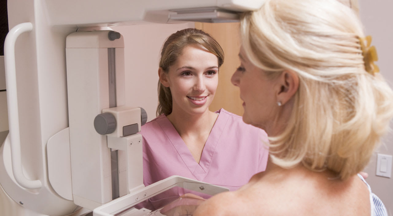 Female mammogram technician smiling at patient.