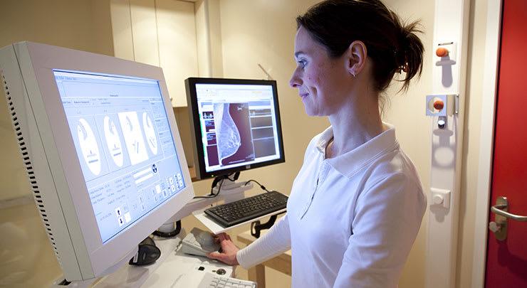 Female mammogram technician examining mammogram report.