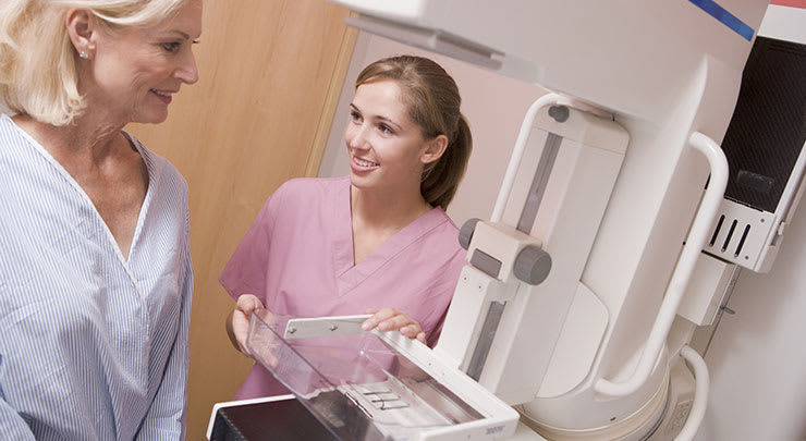 Woman with breast implants getting a mammogram.