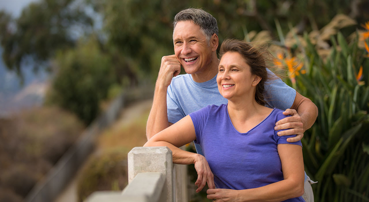 Older woman and man smiling and looking out at the water while wind blows through their hair.