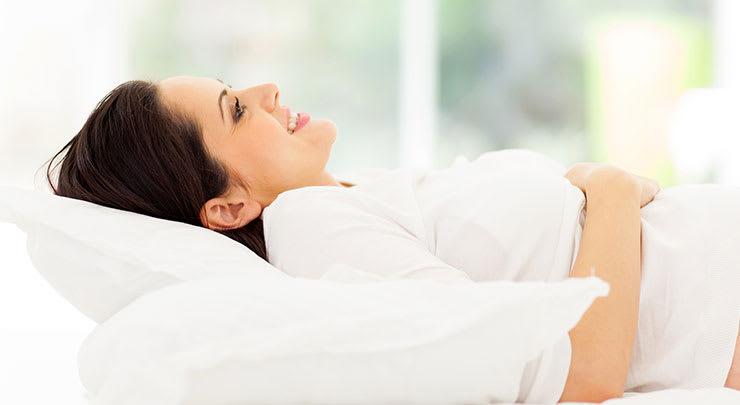 Woman lying down on bed on her back and smiling.