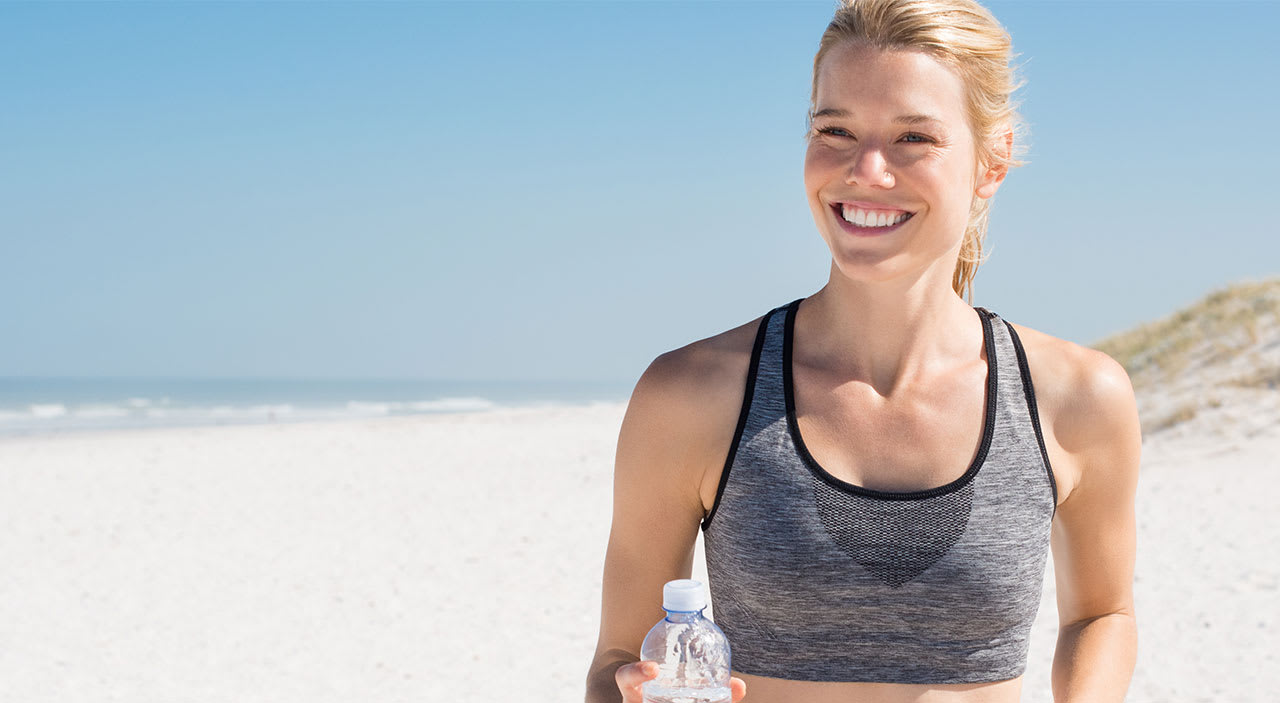 Blonde woman smiling as she runs outside to prepare for her breast lift.