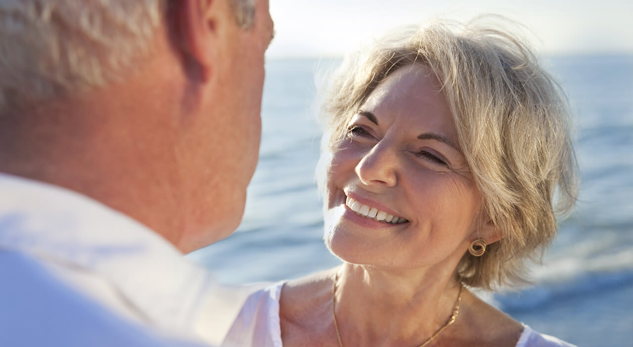 Older blonde woman smiling up at her husband at the beach.