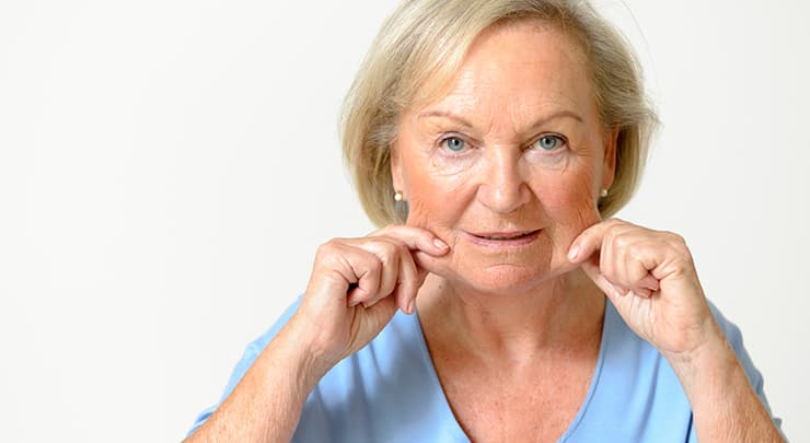 Older woman pinching her saggy jowls.