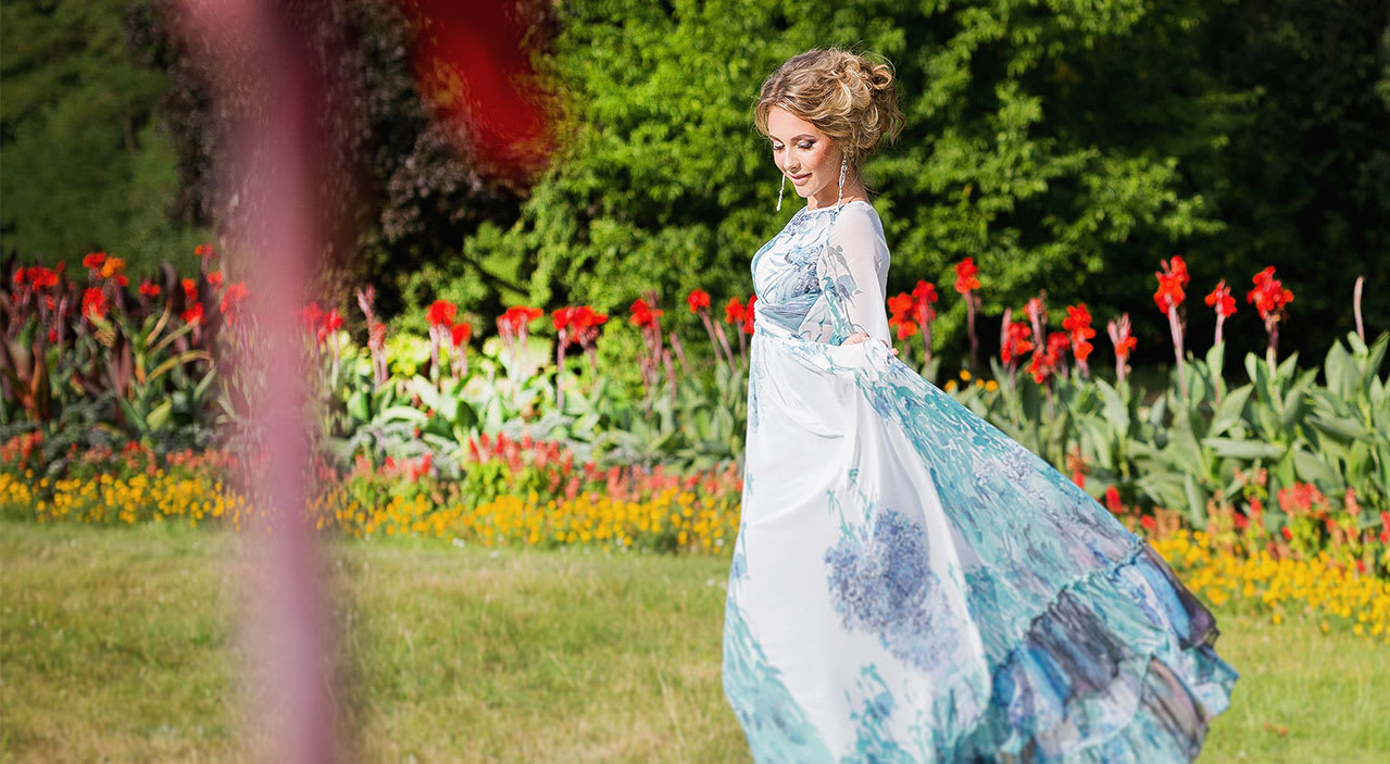 Young woman wearing long dress with hair looking down while standing in green garden with beautiful flowers.