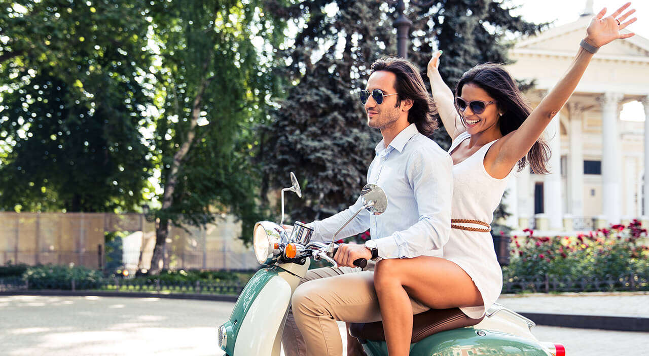 Man on blue motor scooter with woman wearing a white dress sitting behind him and smiling.