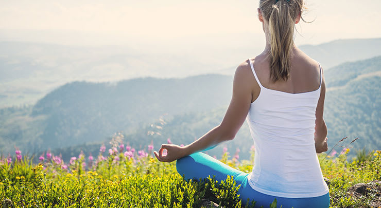 Woman in white tank top and blue pants sitting on grassy mountain meditating after clitoral hood reduction.