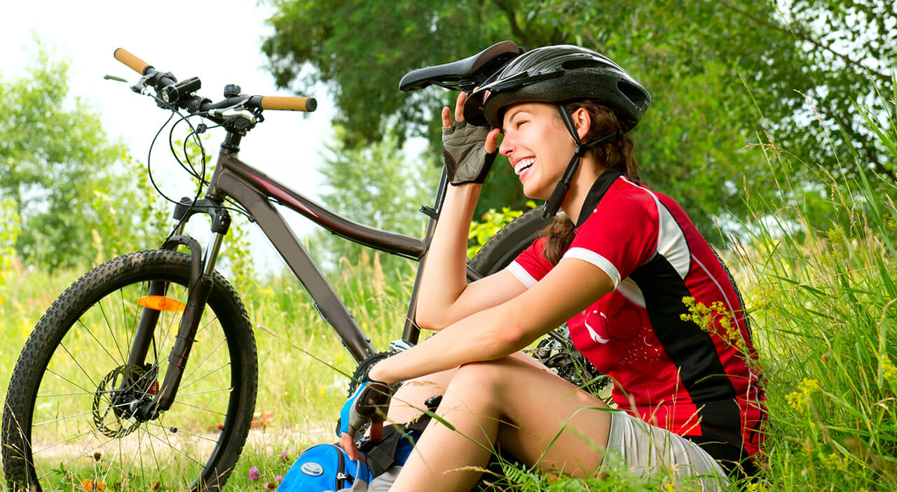 Woman wearing bike helmet sitting on grass beside bike and smiling.