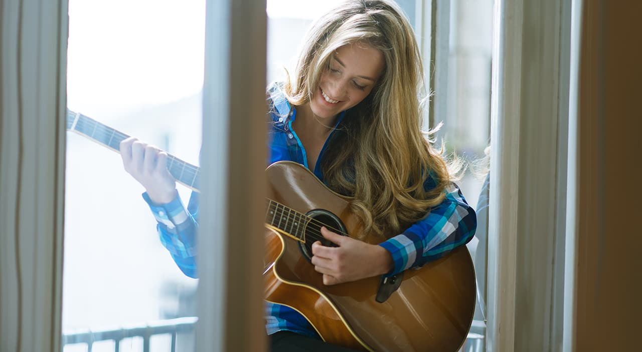 Woman sitting at window playing guitar and smiling.