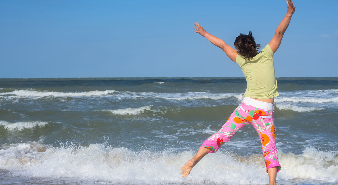 Woman jumping up in happiness at beach.