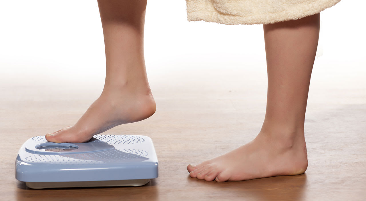Woman stepping on scale to weigh herself.