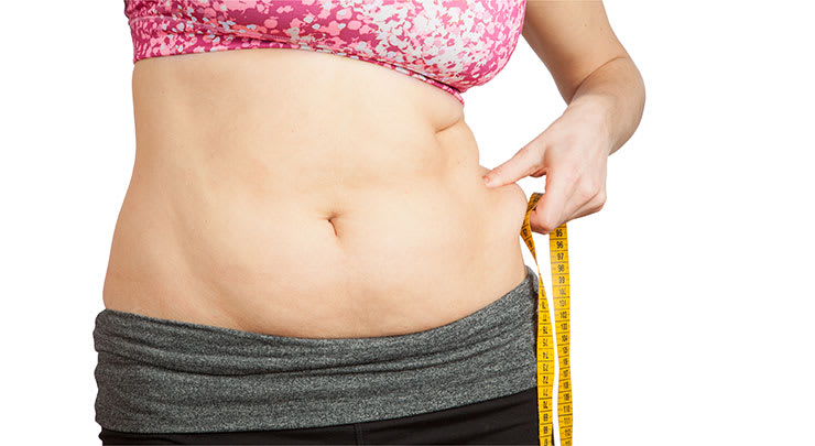 Woman grabbing her loose skin on her stomach.