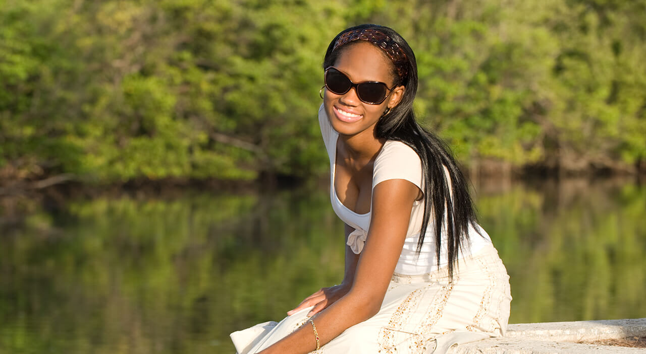 Woman sitting on dock at lake wearing white dress and sunglasses smiling.