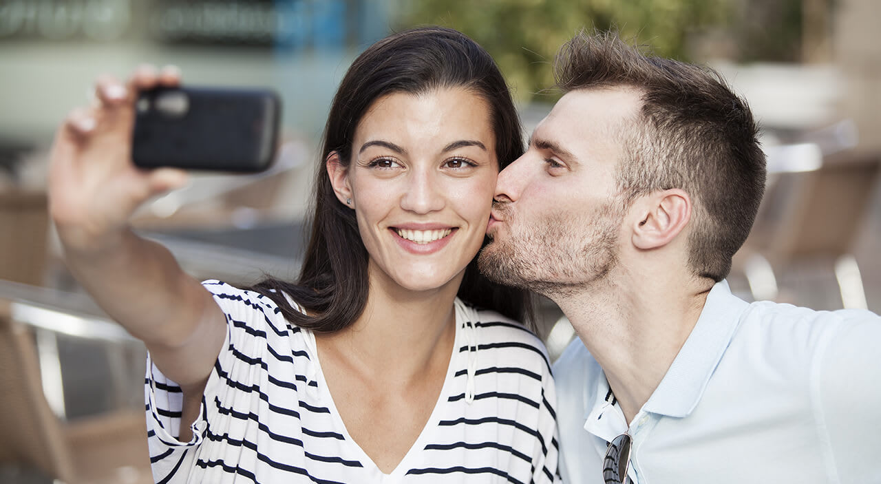 Woman with brown hair taking a selfie with her phone as her boyfriend kisses her on the cheek.