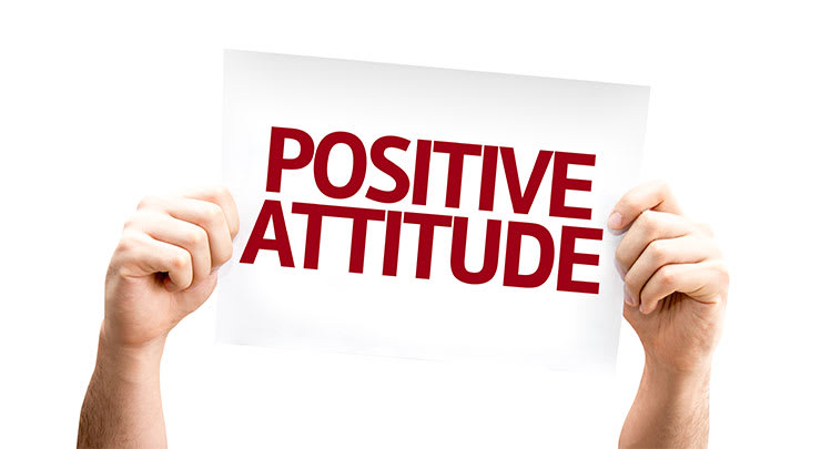 Person holding up sign that says positive attitude for otoplasty.