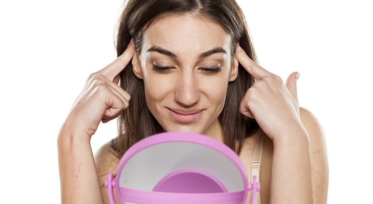 Woman looking at mirror while pushing back her prominent ears.