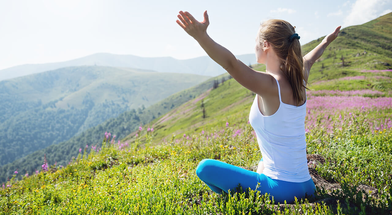 woman sitting on high mountain on the grass looking out with hands upward.
