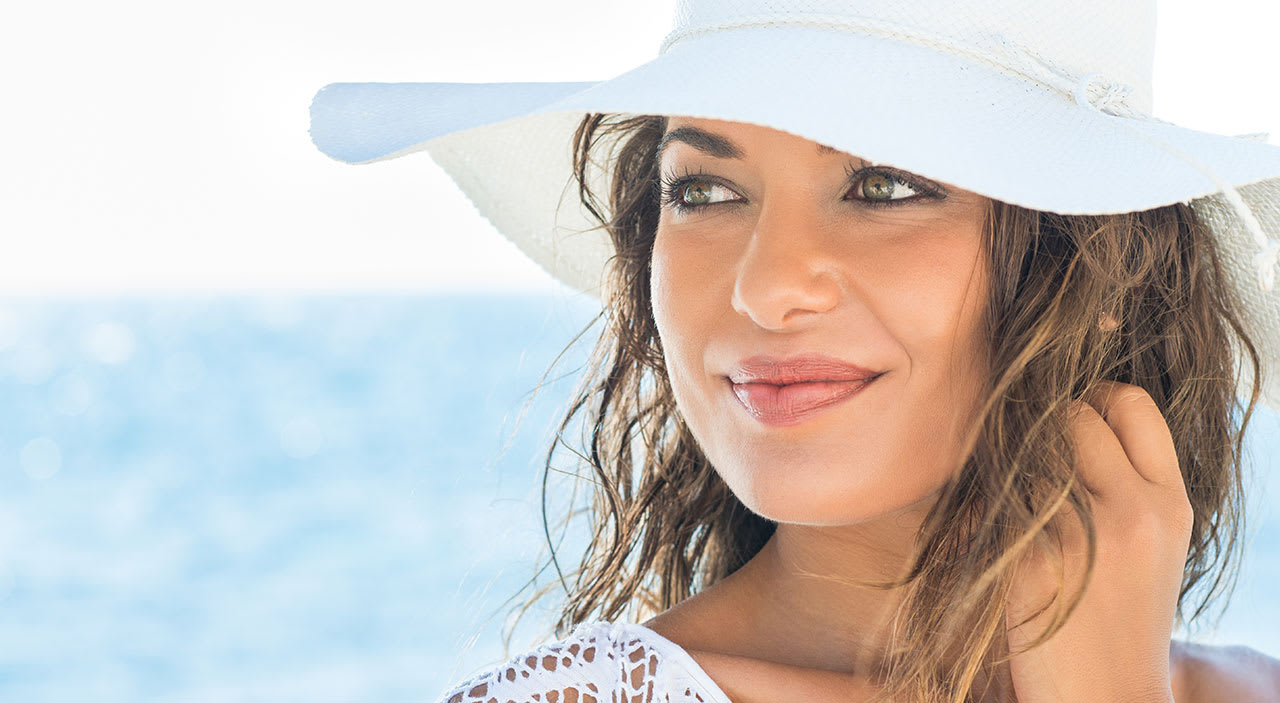 Woman wearing white hat at the beach with beautiful eyes.