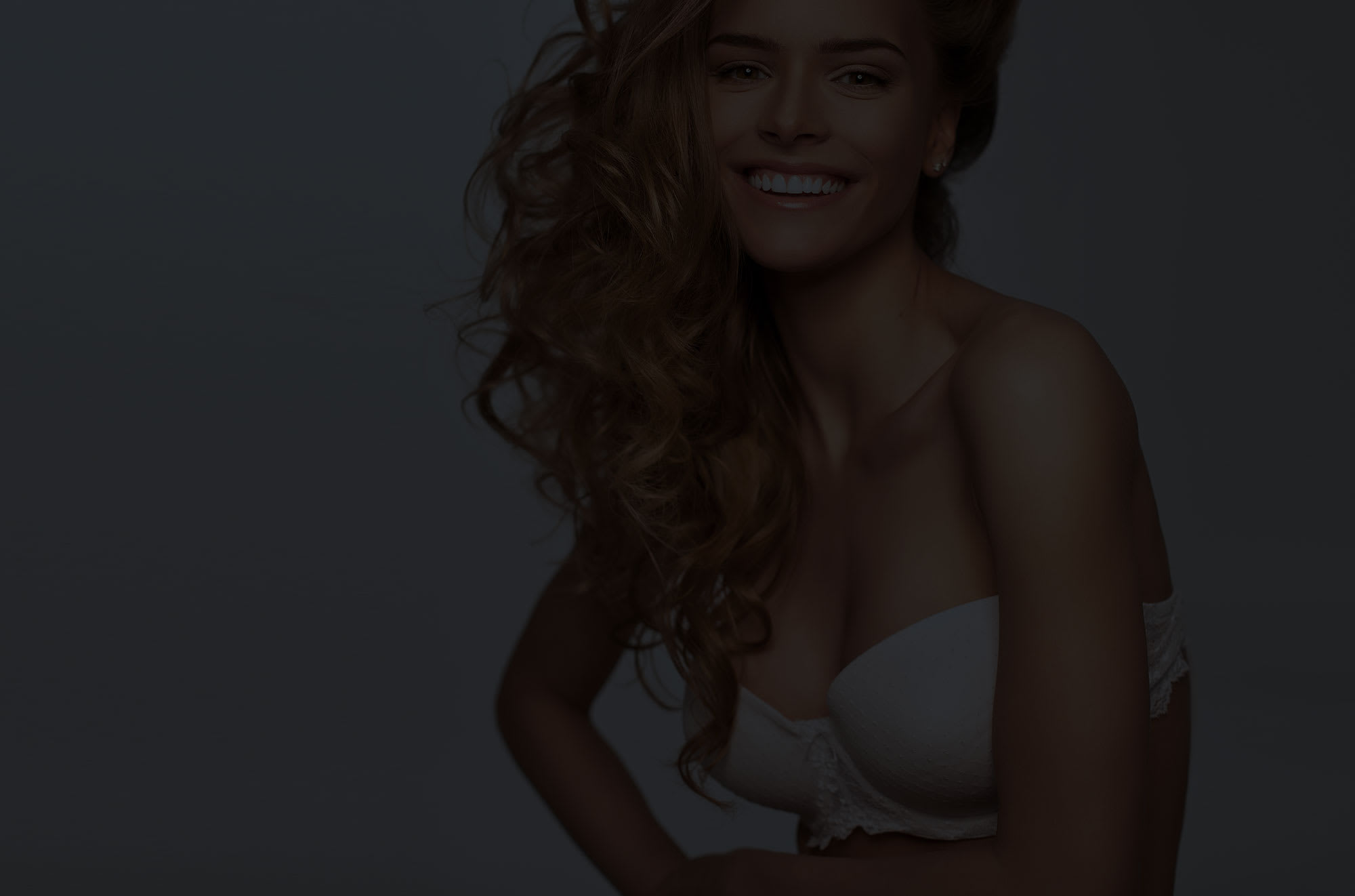 Woman with long blonde hair smiling in bra.