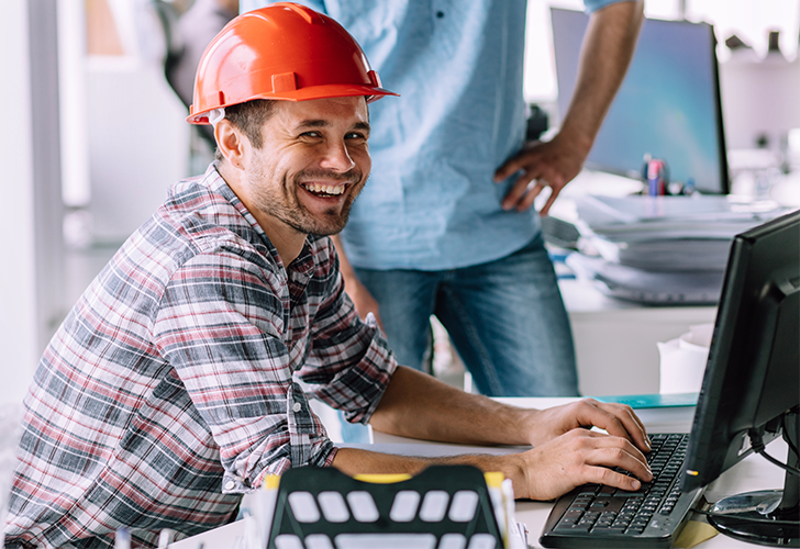 Construction worker sits at computer smiling at camera.