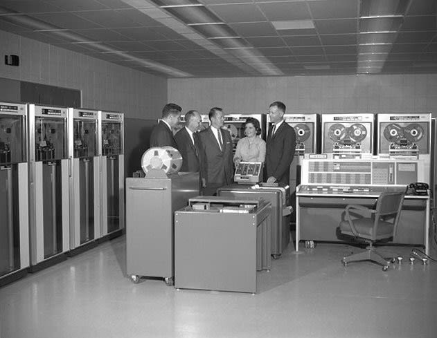Photo of some business people standing around a large 1960s computer