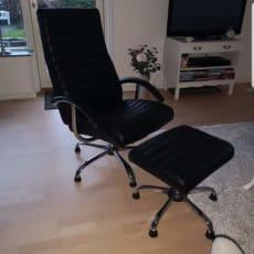 Sort lænestol med skammel og stålhjul sælges