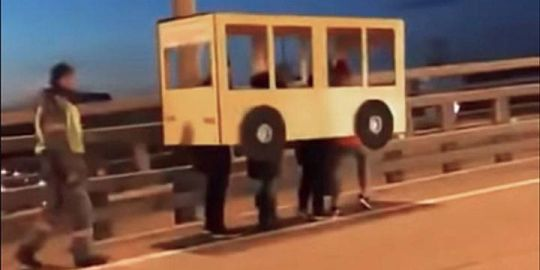 Russians dressed up as a cardboard bus attempt to cross vehicle-only bridge