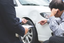 Client and insurance representative inspecting damaged vehicle