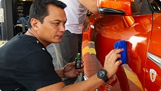 Technician applying wax on vehicle