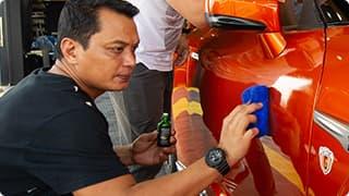 Technician applying wax on car