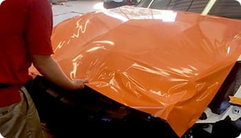 technician working on hood of a car