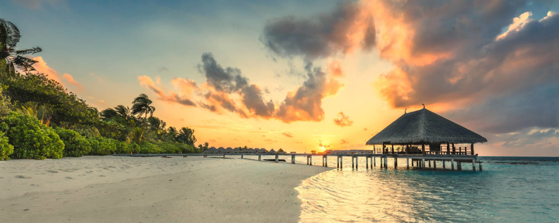 Malediven entdecken mit Tischler Reisen: Malediven Insel Bootsanleger im Sonnenuntergang