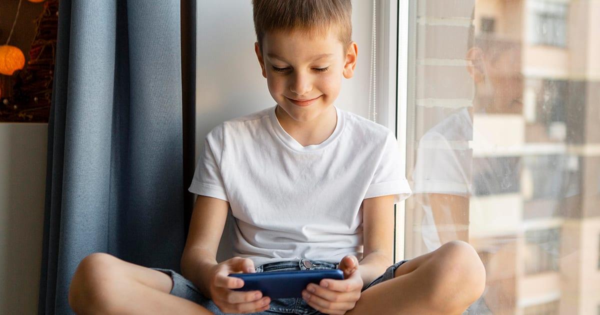 imagem que representa menino aplicando a gamificação na educação com um celular
