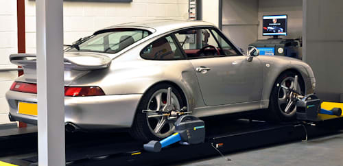 Porsche set up on wheel alignment rack with sensors clamped onto each wheel