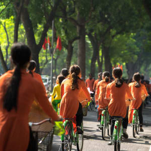 Grosse Indochina Reise ab Hanoi: Hanoi Vietnamese girls wear traditional long dress Ao Dai cycling on street