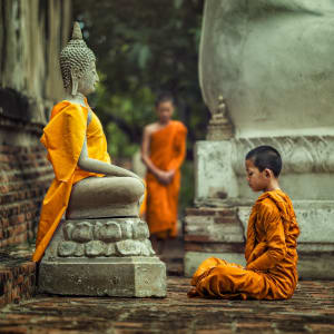 Unbekannter I-San ab Bangkok: Novice monk vipassana meditation at front of Buddha statue