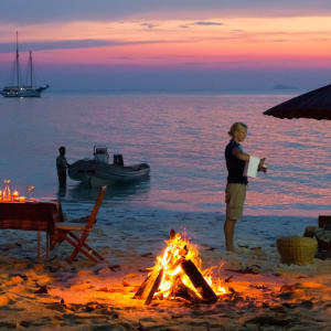 Segeltörn im paradiesischen Mergui Archipel ab Kawthaung: Raja Laut anchoring in rosy sunset by a beach with dinner table and bonfire