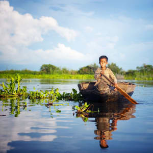 Angkor mystique de Siem Reap: Tonle Sap boy travelling by boat to his floating village