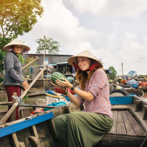 Das Mekong Delta – ab Saigon bis Phnom Penh: Tourist buying fruits from the boat on Cai Rang floating market, Can Tho