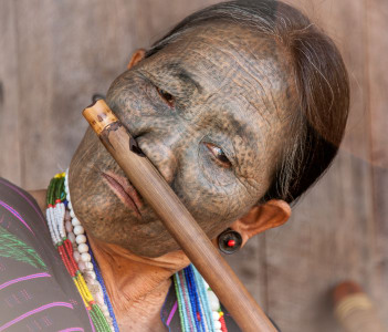 A tattooed face woman playing a typical instrument in Kanpetlet Myanmar