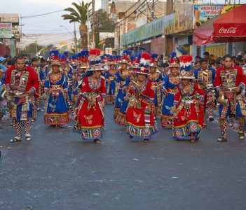 Tinku dancing group in colourful costumes performing a traditional ritual dance in Arica