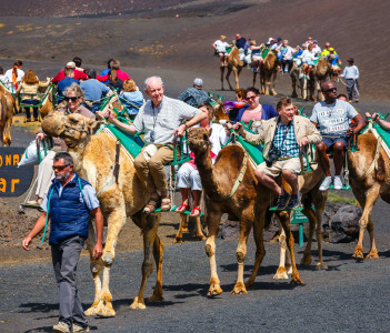 Tourists riding camels in Timanfaya National Park. Camel trek is popular attraction on Lanzarote island.