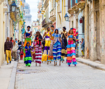 Colorful band of musicians and dancers on stilts on a narrow Old Havana street