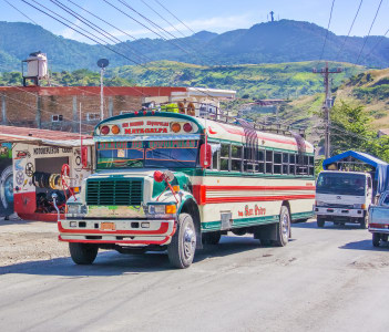 Colorful bus on the road running thru small town of Matagalpa in Nicaragua