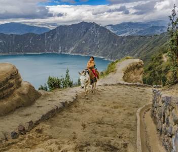 Kid riding a horse at Quilotoa lagoon Ecuador
