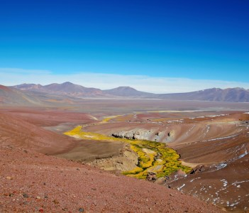Panoramic view  over a green and yellow river between brown sandy hills on the way to Laguna Verde close to Copiapo in Chile, South America