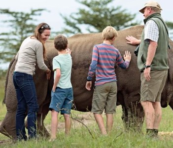 Family touching a tamed rhino