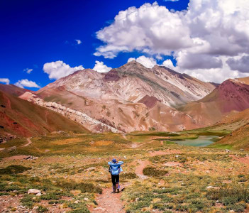 Female trekker walking alone on the trekking path to Aconcagua, highest peak in South America, Argentina
