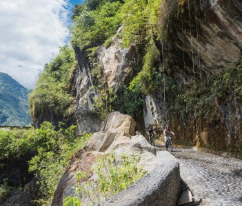 Tourists ride bicycles along the Waterfalls in Cascades route Banos Puyo in Ecuador